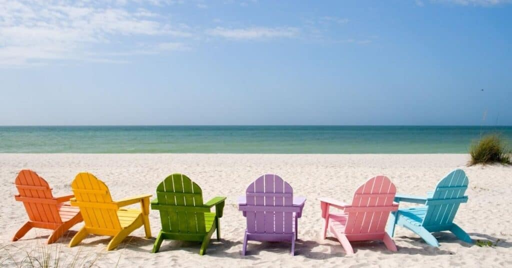 A row on cape cod chairs in rainbow colors on the beach