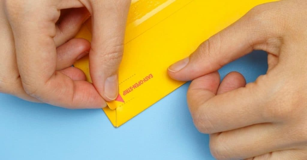 Hand opening an envelope