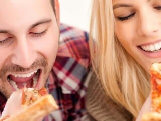 Couple eating a piece of pizza each on their Friday night dinner date night.