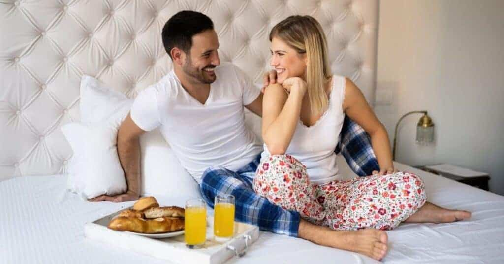 Couple sitting on bed in their pjs about to have breakfast in bed as one of their bedroom date ideas.