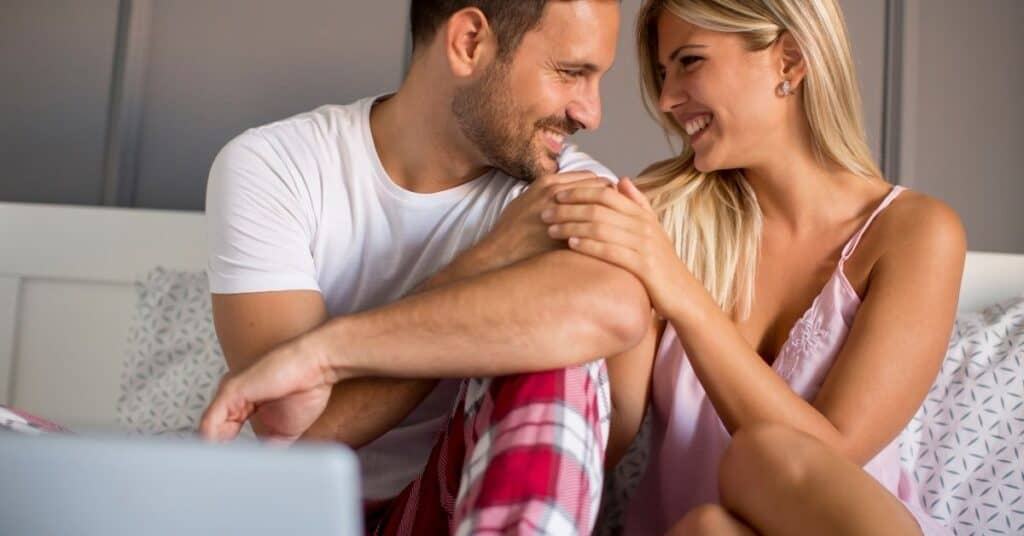 Couple talking in bed after watching a ted talk as one of their bedroom date ideas.
