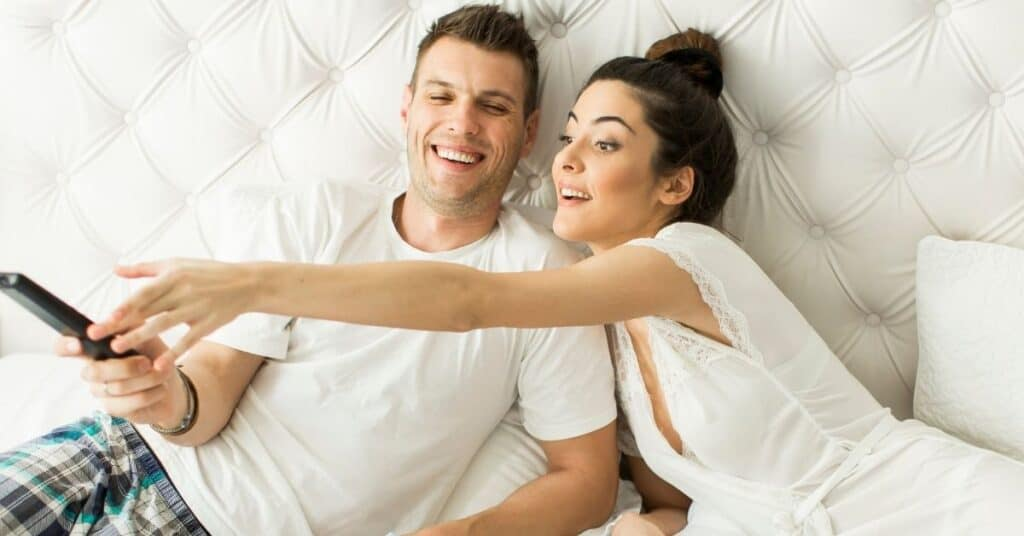 Couple having fun with the remote during a stay in bed date.