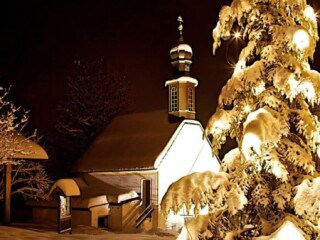 A small church lit up with Christmas lights