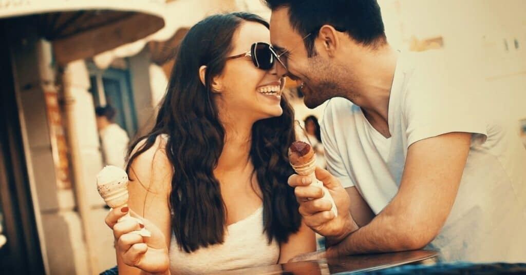 Couple kissing while holding ice cream during a cheap date