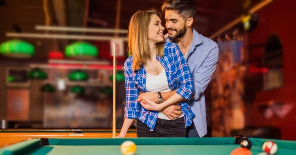 Couple standing in front of a pool table.