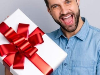 Man with a cheesy grin holding a gift.