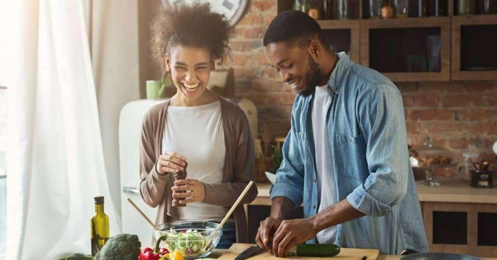 Black couple cooking together.