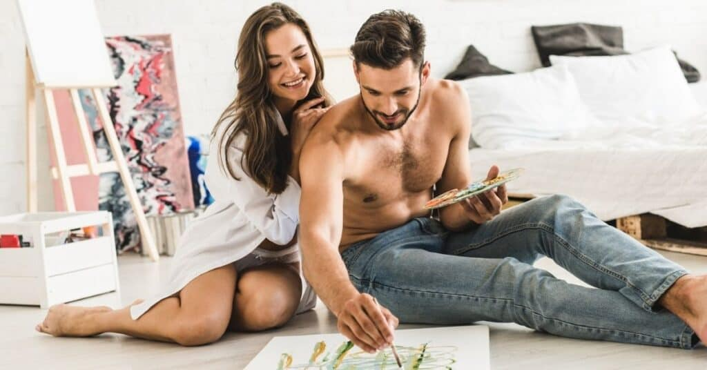 Couple sitting on floor of bedroom completing a painting as one of the hobbies for couples.