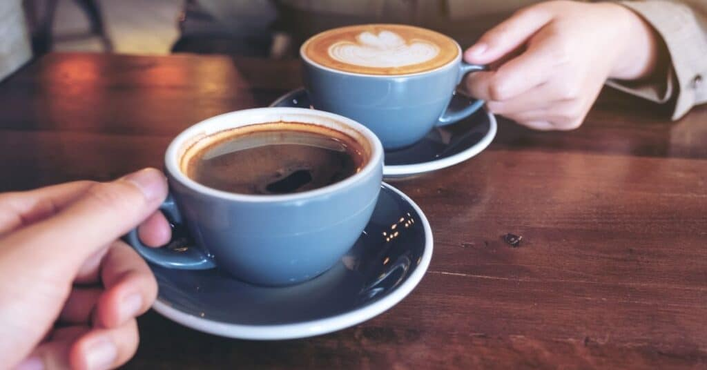 Couple's hands holding two cups of coffee
