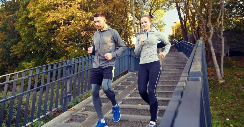 Couple running down the stairs together during a morning jog