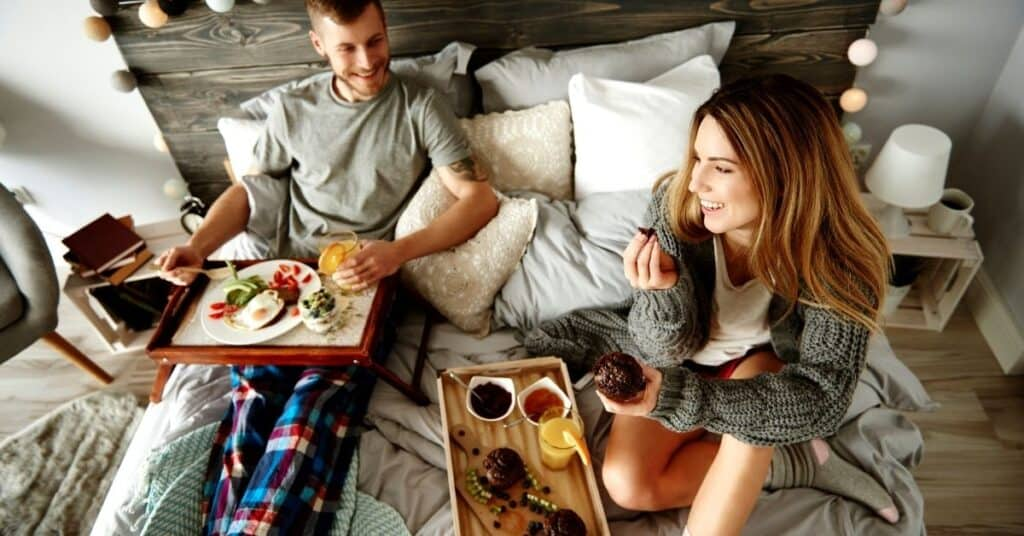 Couple eating breakfast in bed as a last minute date idea at home.