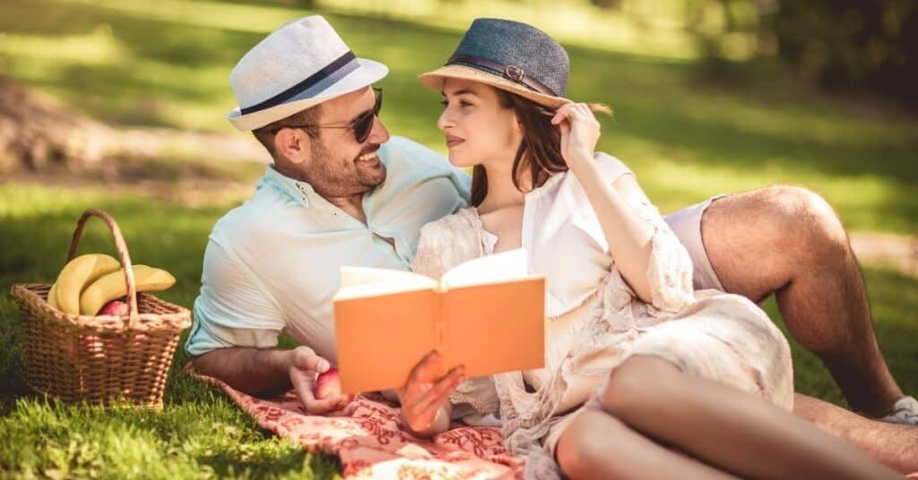 Couple sitting on a blanket, reading books.