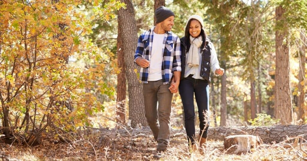 Couple walking in the woods for a quick date idea.