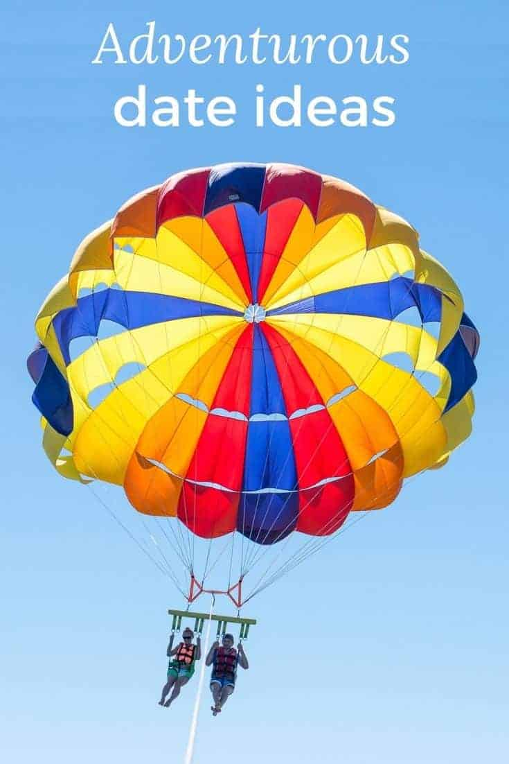 Couple parasailing with a brightly colored balloon on a deep blue sky. The text reads Adventurous date ideas.