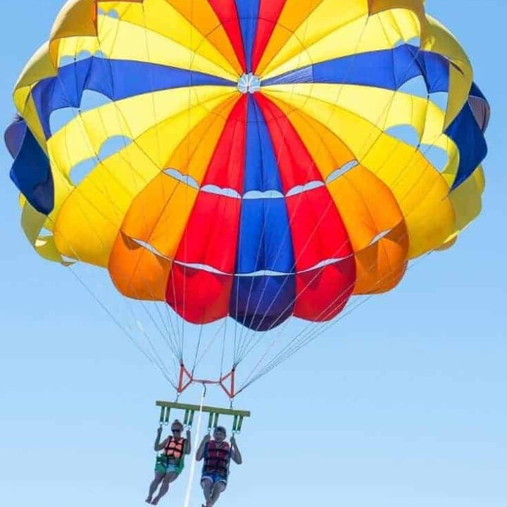 Couple parasailing with a brightly colored balloon on a deep blue sky.