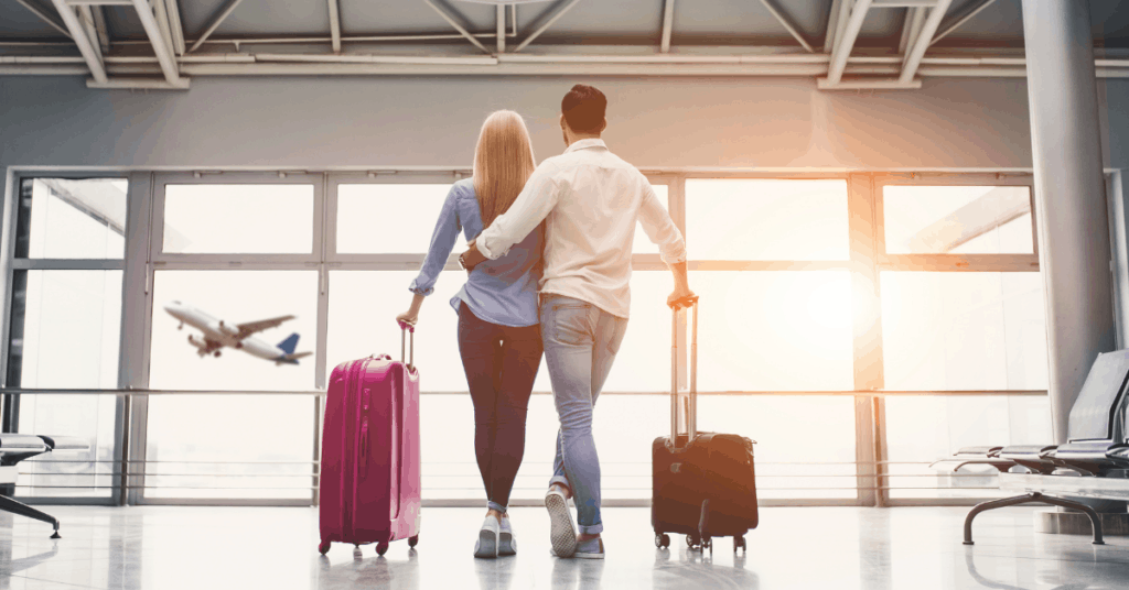 couple standing in the airport, holdig their suitcases looking out the window
