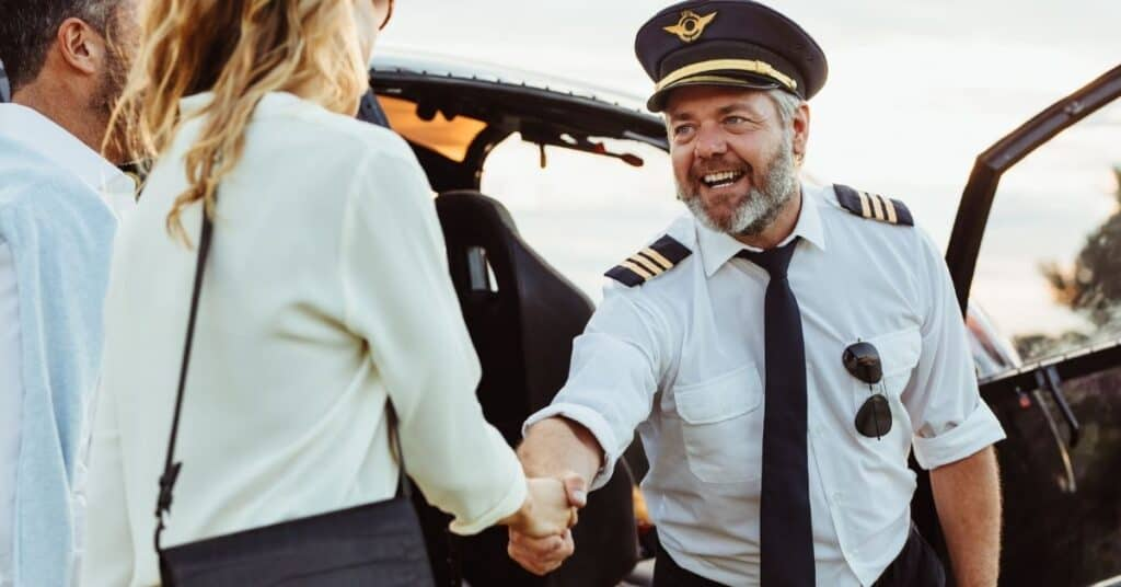 Helicopter pilot shaking hand of couple having a ride as one of their adventurous date ideas.