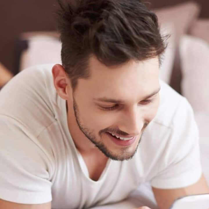 Man lying on the bed reading a good morning text