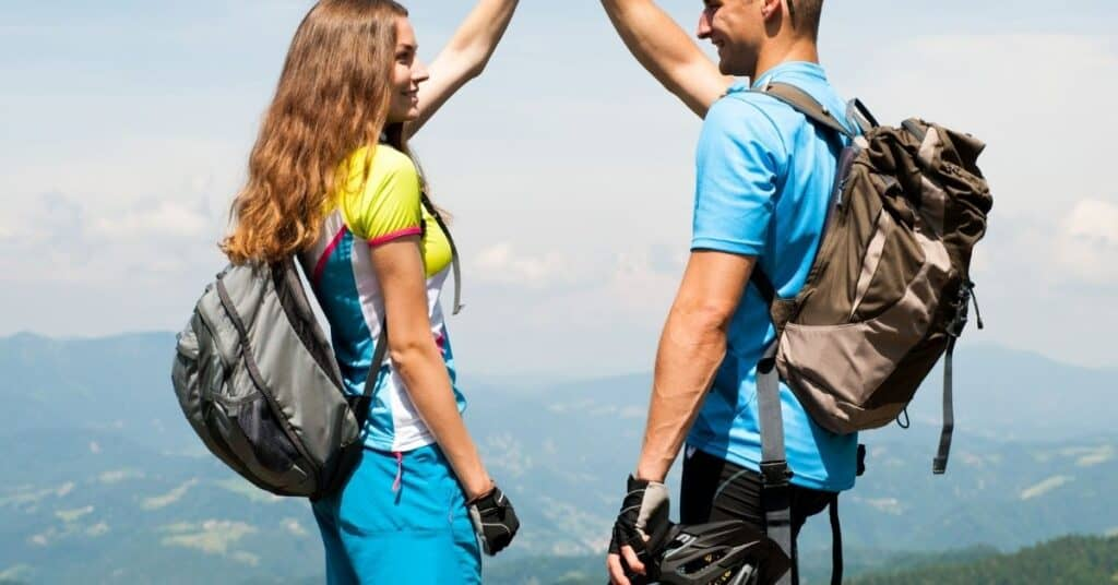 Couple high fiving each other after finishing hike.